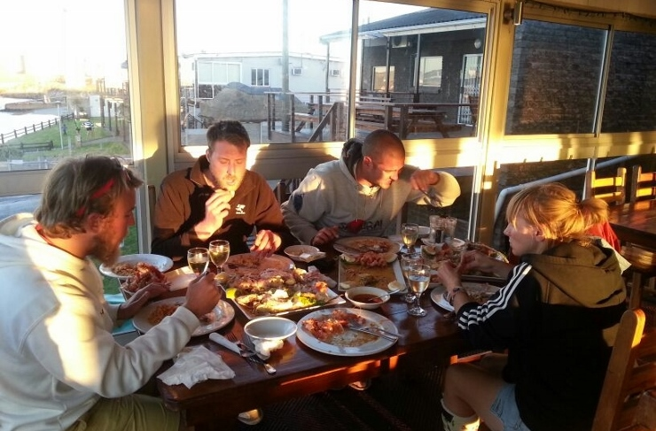 Guests from our Fishing Charters enjoying their catch prepared and cooked at the Yacht Club